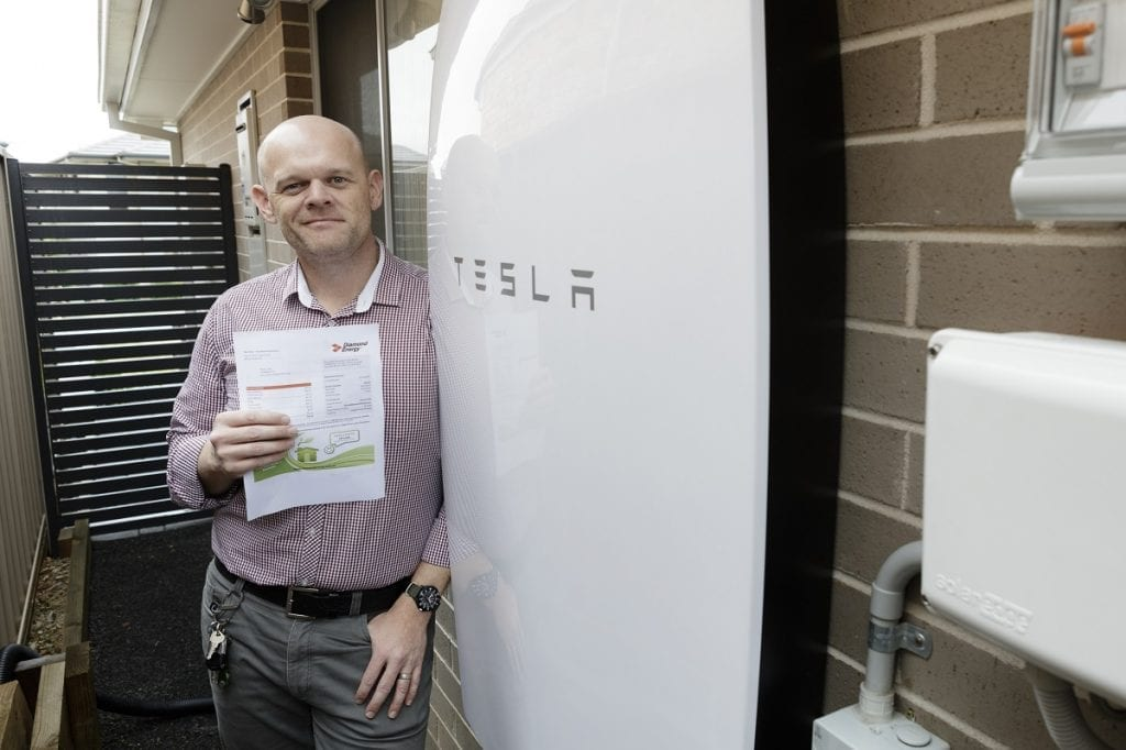 Nick Pfitzner showing off his $50 power bill in front of his Tesla Powerwall Installation by Natural Solar