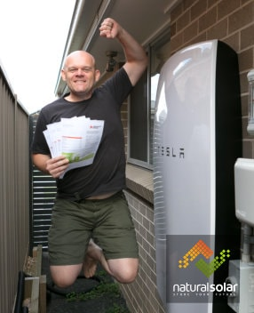 Nick Pfitzner jumps for joy with his Tesla Powerwall home battery.